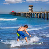 Boy surfer surfing waves on Huntington beach — Stock Photo
