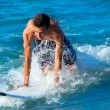 Boy surfer surfing waves on the beach — Stock Photo