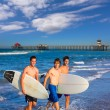 Boys surfers group coming out from beach — Stockfoto