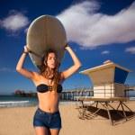 Brunette surfer teen girl holding surfboard in a beach — Stock Photo #30643993