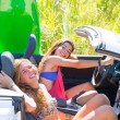 Happy crazy teen surfer girls smiling on car — Stock Photo