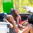 Happy crazy teen surfer girls smiling on car — Stock Photo #30644367