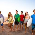 Surfer teen boys girls group walking on beach — Stock Photo #30645573