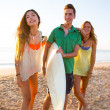 Surfer girls with teen boy walking on beach shore — Stock Photo #30645925
