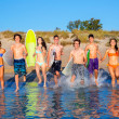 Teen surfers group running beach splashing — Stock Photo