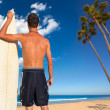 Boy surfer back view holding surfboard on beach — Stock Photo