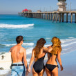 Surfers boys and girls walking rear view on beach — Stock Photo #30647555