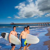 Boys surfers group coming out from beach — Stock Photo