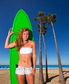 Blond surfer teen girl holding surfboard on beach — Stock Photo