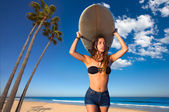 Brunette surfer teen girl holding surfboard in a beach — Stock Photo