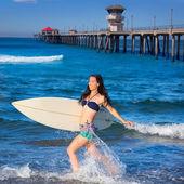 Brunette surfer girl running in the beach — Stock Photo