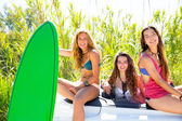 Surfer girls group holding happy surfboards on convertible car — Stock Photo