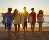 Surfers boys and girls group walking on beach — Stock Photo