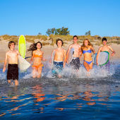 Teenager surfers group running beach splashing — Stock Photo