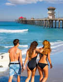 Surfers boys and girls walking rear view on beach — Stock Photo