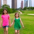 Two girls friends walking holding hand in urban skyline — Stock Photo #32482911