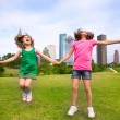 Two girls friends jumping happy holding hand in city skyline — Stock Photo