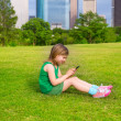 Blond kid girl playing with smartphone sitting on park lawn at c — Stock Photo #32484775