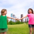 Two sister girls friends playing holding hand in urban skyline — Stock Photo #32484795
