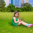 Blond kid girl playing with smartphone sitting on park lawn at c — Stock Photo #32484931