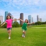 Two sister girls friends running holding hand in urban skyline — Stock Photo
