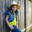 Children girl as kid cowgirl posing on wooden fence — Stock Photo