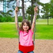 Brunette kid girl playing with swing on city park — Stock Photo