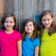 Sister and friends kid girls portrait smiling on gray fence — Stock Photo