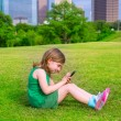 Blond kid girl playing with smartphone sitting on park lawn at c — Stock Photo