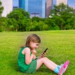 Blond kid girl playing with smartphone sitting on park lawn at c — Stock Photo #32487827