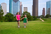 Two sister girls friends running holding hand in urban skyline — Stock Photo