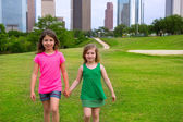 Two girls friends walking holding hand in urban skyline — Stock Photo