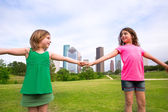 Two sister girls friends playing holding hand in urban skyline — Stock Photo