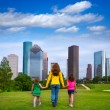 Mother and daughters walking holding hands on city skyline — Stockfoto