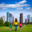 Mother and daughters walking holding hands on city skyline — 图库照片