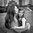Mother and daughter happy hug kiss in park at city skyline — Stock Photo