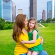 Mother and daughter happy hug in park at city skyline — Stock Photo