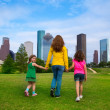 Mother and daughters walking holding hands on city skyline — Stock Photo