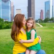 Mother and daughter happy hug in park at city skyline — Stock Photo #32492007