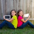Twin sister girls playing tablet pc sitting on backyard lawn — Stock Photo #32492267