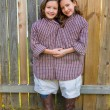 Stock Photo: Twin girls dressed up as siamese with his father shirt