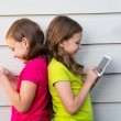 Twin sister girls playing with tablet pc happy on white wall — Stock Photo