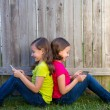 Twin sister girls playing tablet pc sitting on backyard lawn — Stock Photo #32493849