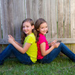 Twin sister girls playing tablet pc sitting on backyard lawn — Stock Photo