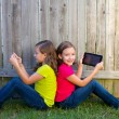 Twin sister girls playing tablet pc sitting on backyard lawn — Stock Photo #32494017