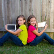 Twin sister girls playing tablet pc sitting on backyard lawn — Stock Photo #32494119