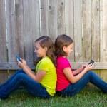 Twin sister girls playing smartphone sitting on backyard lawn — Stock Photo