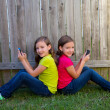 Twin sister girls playing smartphone sitting on backyard lawn — Stock Photo