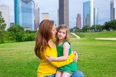 Matka i córka szczęśliwy uścisk w parku w panoramę miasta — Zdjęcie stockowe