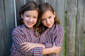 Twin girls dressed up as siamese with his father shirt — Stock Photo